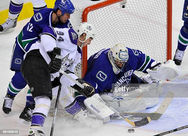 Goalie Roberto Luongo of the Vancouver Canucks stops Ryan Smyth of the Los Angeles Kings as Kyle Wellwood of the Canucks tries to help stop Smyth on...