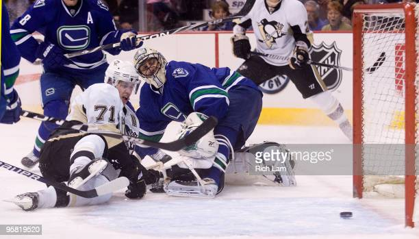 Goalie Roberto Luongo of the Vancouver Canucks watches Evgeni Malkin of the Pittsburgh Penguins' shot slide into the net during the first period of...