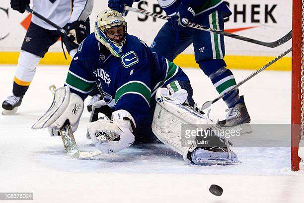 Goalie Roberto Luongo of the Vancouver Canucks watches the puck roll into the corner after making a pad save against the Nashville Predators during...