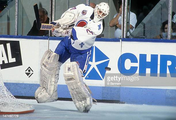 Goalie Ron Hextall of the Quebec Nordiques passes the puck during an NHL game circa 1993 at the Quebec Coliseum in Quebec City Quebec Canada