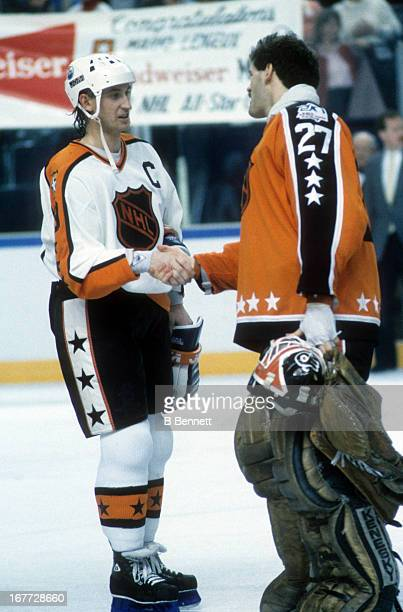 Goalie Ron Hextall of the Wales Conference and the Philadelphia Flyers shakes hands with Wayne Gretzky of the Campbell Conference and the Edmonton...