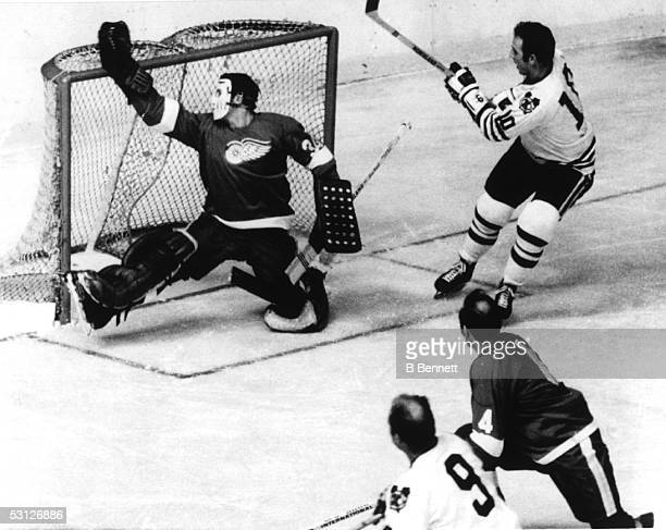 Goalie Roy Edwards of the Detroit Red Wings makes a save on Dennis Hull of the Chicago Black Hawks as Bobby Hull looks for the rebound during their...