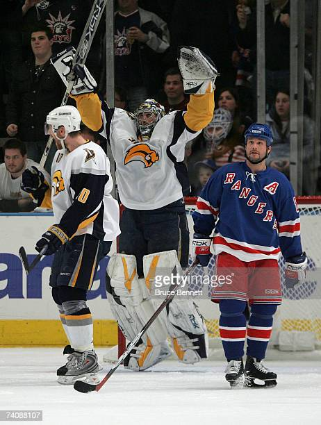 Goalie Ryan Miller of the Buffalo Sabres and teammate Henrik Tallinder celebrate their 54 victory as Martin Straka of the New York Rangers skates...