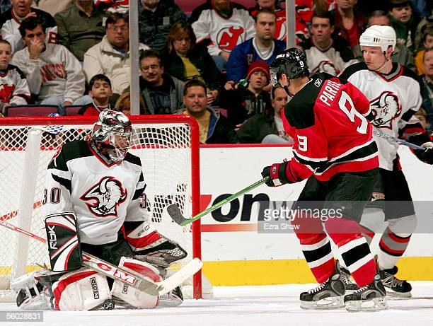 Goalie Ryan Miller of the Buffalo Sabres makes a save on a shot by Zach Parise of the New Jersey Devils as defenseman Dmitri Kalinin of the Sabres...