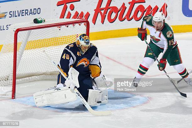 Goalie Ryan Miller of the Buffalo Sabres stops the puck against Andrew Brunette of the Minnesota Wild at HSBC Arena on March 12 2010 in Buffalo New...