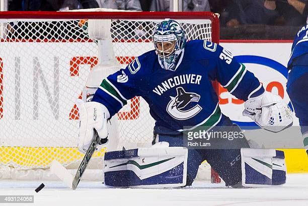 Goalie Ryan Miller of the Vancouver Canucks clears the puck during NHL action against the Calgary Flames on October 10 2015 at Rogers Arena in...