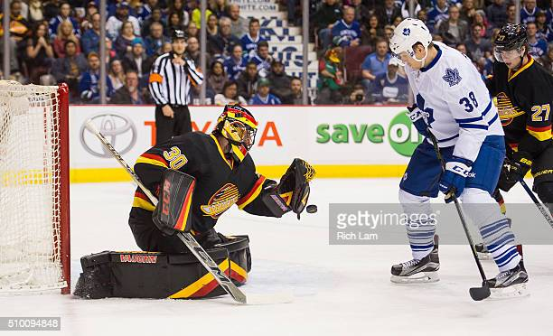 Goalie Ryan Miller of the Vancouver Canucks knocks the puck away while Colin Greening of the Toronto Maple Leafs looks for a rebound in NHL action on...