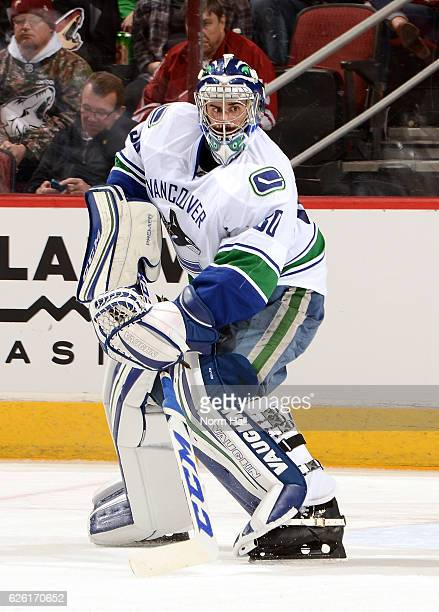 Goalie Ryan Miller of the Vancouver Canucks passes the puck up ice against the Arizona Coyotes at Gila River Arena on November 23 2016 in Glendale...
