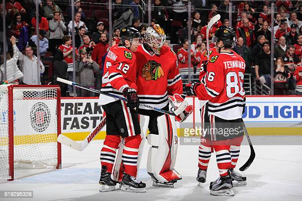 Goalie Scott Darling and Tomas Fleischmann of the Chicago Blackhawks celebrate after defeating the Arizona Coyotes 6 to 2 during the NHL game at the...