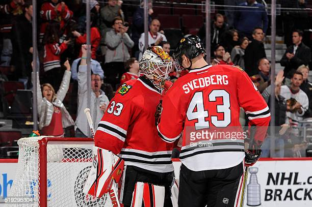Goalie Scott Darling and Viktor Svedberg of the Chicago Blackhawks celebrate after defeating the Arizona Coyotes 6 to 2 during the NHL game at the...