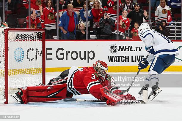 Goalie Scott Darling of the Chicago Blackhawks blocks the shot taken by Mitchell Marner of the Toronto Maple Leafs in the shootout at the United...