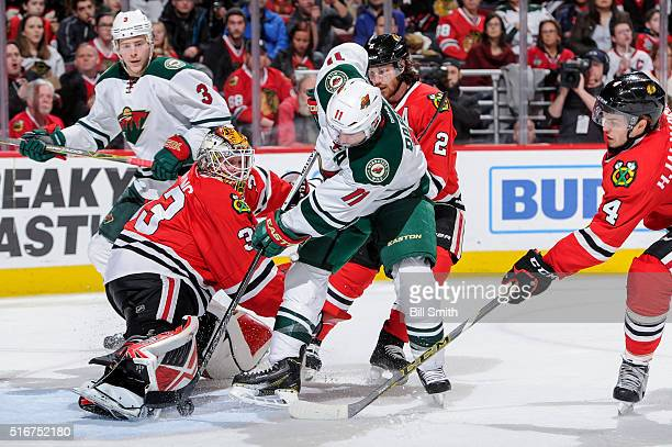 Goalie Scott Darling of the Chicago Blackhawks stops the shot from Zach Parise of the Minnesota Wild as Niklas Hjalmarsson reaches across and Charlie...