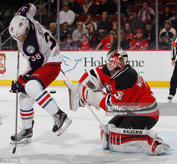 Goalie Scott Wedgewood of the New Jersey Devils plays a tip shot by Boone Jenner of the Columbus Blue Jackets during the first period of an NHL...