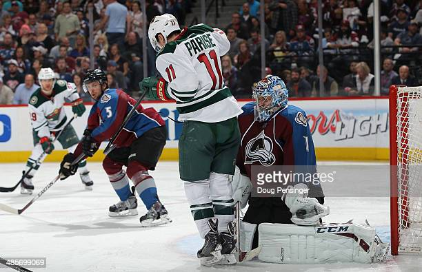 Goalie Semyon Varlamov of the Colorado Avalanche makes a glove save behind Zach Parise of the Minnesota Wild in Game Two of the First Round of the...