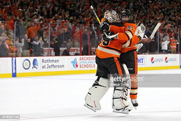 Goalie Steve Mason and teammate Jakub Voracek of the Philadelphia Flyers celebrate after defeating the Washington Capitals at Wells Fargo Center on...