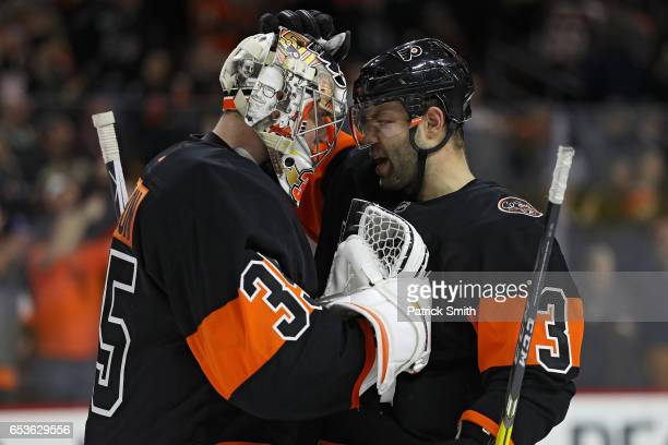 Goalie Steve Mason of the Philadelphia Flyers celebrates with teammates Radko Gudas after defeating the Pittsburgh Penguins during the third period...