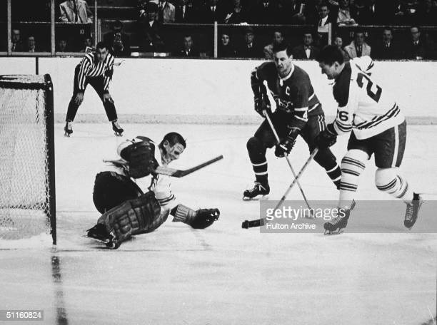 Goalie Terry Sawchuk of the Toronto Maple Leafs makes the save on the shot by Jean Beliveau of the Montreal Canadiens as Allan Stanley of the Maple...