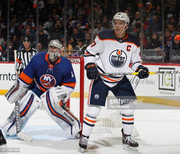 Goalie Thomas Greiss of the New York Islanders defends the goal as Connor McDavid of the Edmonton Oilers'nwaits for a pass in an NHL hockey game at...