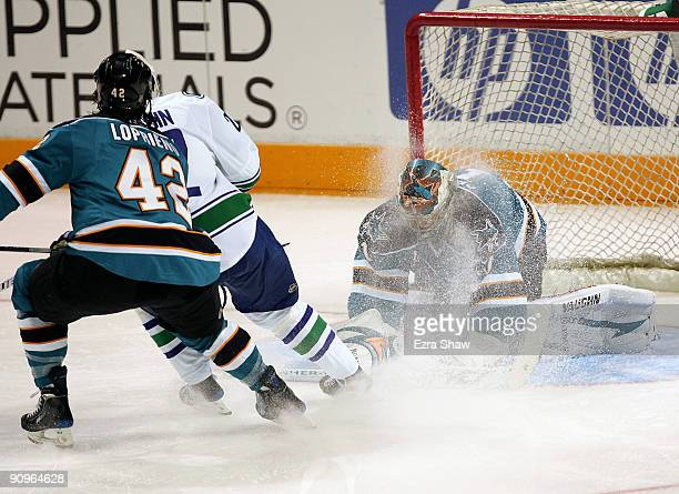 Goalie Thomas Greiss of the San Jose Sharks makes a save on a shot taken by Daniel Sedin of the Vancouver Canucks as Joe Loprieno plays defense for...
