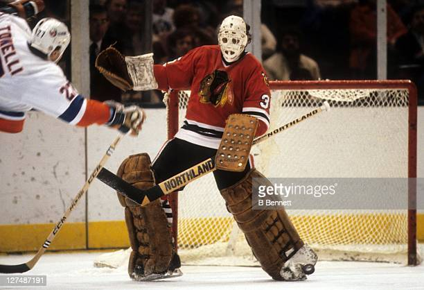 Goalie Tony Esposito of the Chicago Blackhawks looks to make the toe save on John Tonelli of the New York Islanders on November 20 1982 at the Nassau...