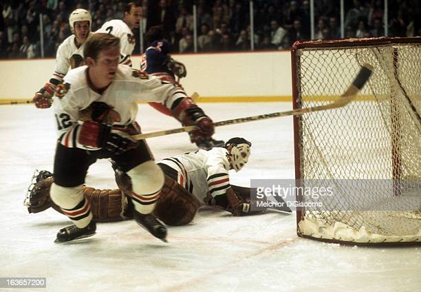 Goalie Tony Esposito of the Chicago Blackhawks made the save as teammate Pat Stapleton goes for the puck during an NHL game against the New York...