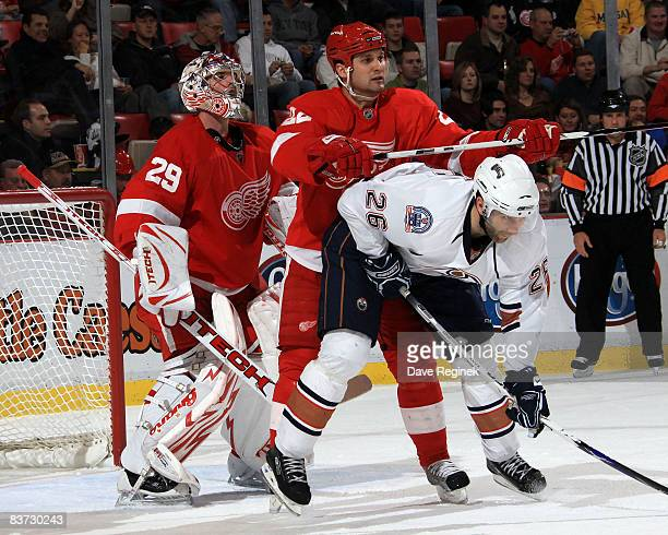 Goalie Ty Conklin of the Detroit Red Wings tries to look over teammate Brad Stuart while Erik Cole of the Edmonton Oilers fights for position during...