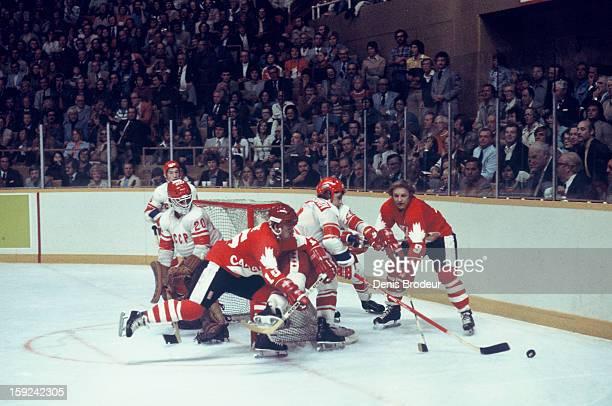 Goalie Vladislav Tretiak looks on while Zinetula Bilyaletdinov and Vladimir Repnev of the of the Soviet Union team fight for the puck against Marcel...