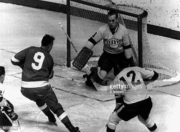 Goalie Wayne Rutledge of the Los Angeles Kings makes the save on Gordie Howe of the Detroit Red Wings as Brian Campbell of the Kings follows the play...