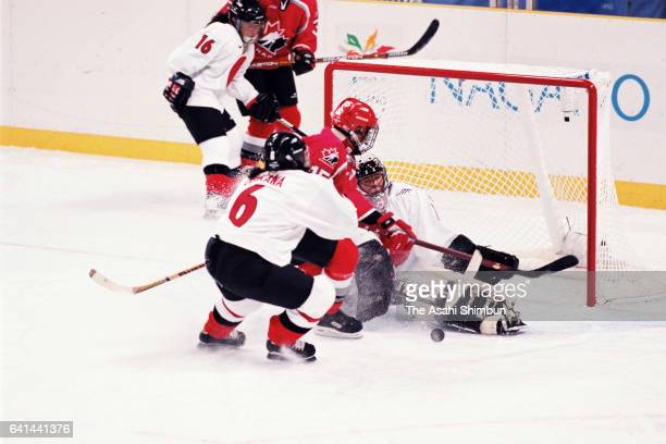 Goalie Yuka Oda of Japan saves a shot by Danielle Goyette of Canada during the Women's Ice Hockey first round match between Japan and Canada during...