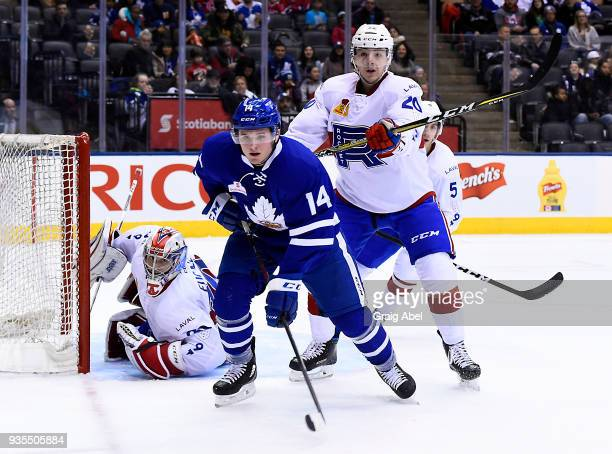 Goalie Zachary Fucale and Etienne Boutet of the Laval Rocket defend against Adam Brooks of the Toronto Marlies during AHL game action on March 12...