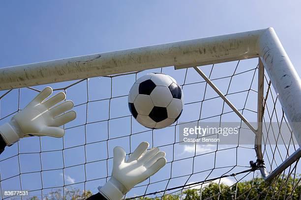 a goalie's hands reaching for a soccer ball - torpfosten stock-fotos und bilder