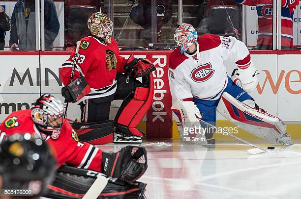 Goalies Scott Darling of the Chicago Blackhawks and Mike Condon of the Montreal Canadiens warm up prior to the NHL game at the United Center on...