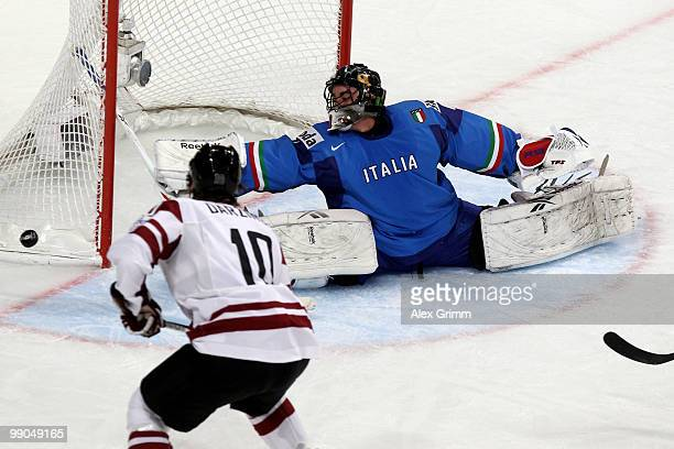 Goalkeeper Adam Russo of Italy makes a save against Aleksandrs Nizivijs of Latvia during the IIHF World Championship group C match between Italy and...