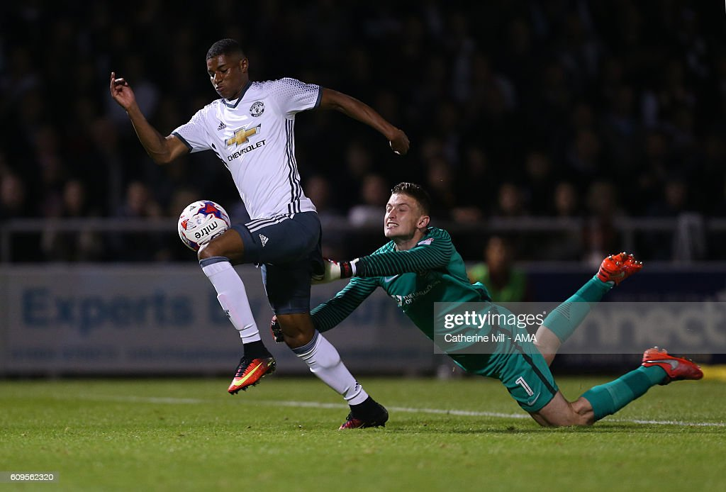 Goalkeeper Adam Smith of Northampton Town tries to hang on to Marcus Rashford of Manchester United as he goes past and scores to make it 1-3 during the EFL Cup match between Northampton Town and Manchester United at Sixfields on September 21, 2016 in Northampton, England.