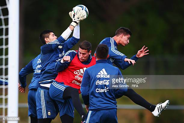Goalkeeper Agustin Rossi is challenged by Jose Devecchi and Lucas Suarez during an Argentina U20s training session at Porirua Park on June 1 2015 in...