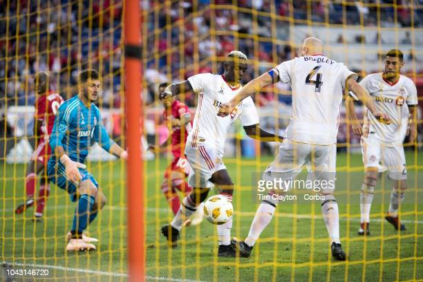 Goalkeeper Alex Bono of Toronto FC and defenders Chris Mavinga of Toronto FC and Michael Bradley of Toronto FC can't stop a low shot from Alejandro...