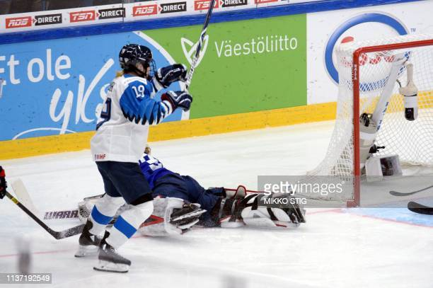 Goalkeeper Alex Rigsby of the United States lies on the ice while Petra Nieminen of Finland starts celebrating her gamewinning overtime goal which...