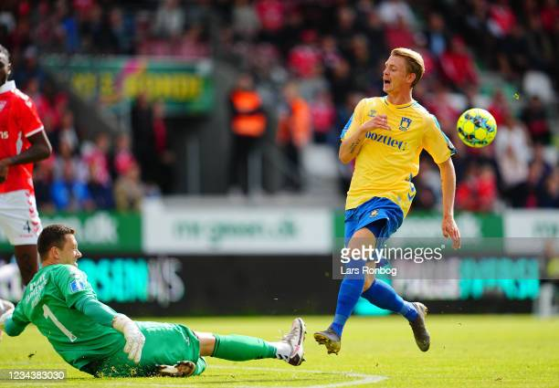 Goalkeeper Alexander Brunst-Zollner of Vejle Boldklub and Simon Hedlund of Brondby IF compete for the ball during the Danish 3F Superliga match...