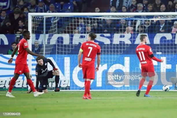 Goalkeeper Alexander Nuebel of Schalke reacts as Timo Werner of Leipzig celebrates his team's second goal during the Bundesliga match between FC...