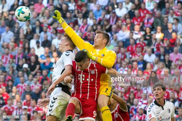 Goalkeeper Alexander Schwolow of Freiburg saves against Robert Lewandowski of Bayern Muenchen during the Bundesliga match between FC Bayern Muenchen...