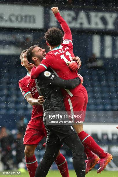 Goalkeeper Alisson Becker of Liverpool celebrates after scoring a goal to make it 1-2 during the Premier League match between West Bromwich Albion...