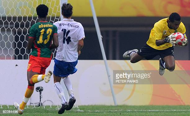 Goalkeeper Amour Tignyemb of Cameroon catches the ball beside of his teammate Gustave Bebbe and Robert Acquafresca of Italy during their 2008 Beijing...