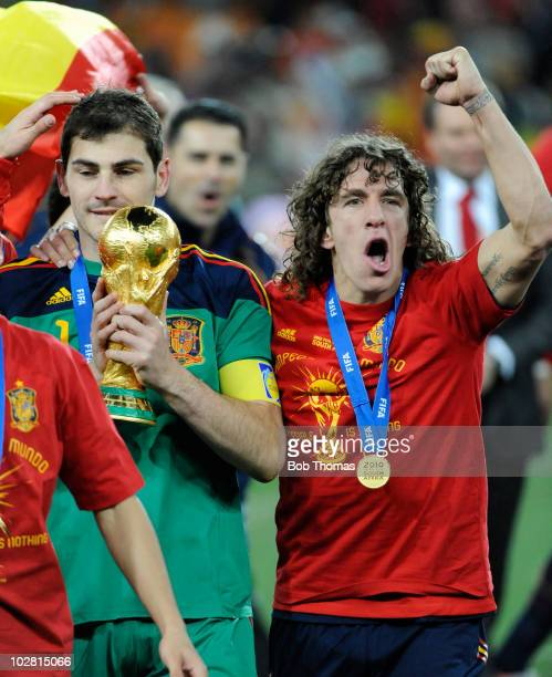 Goalkeeper and captain Iker Casillas of Spain holds the World Cup with Carles Puyol as they celebrate after the 2010 FIFA World Cup Final between the...