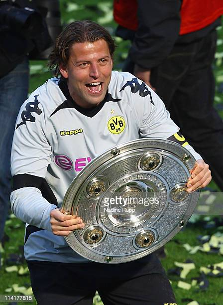 Goalkeeper and captain Roman Weidenfeller of Dortmund rises the trophy and celebrates winning the German Championship after the Bundesliga match...