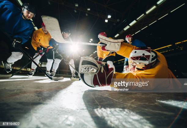 goalkeeper and ice hockey players in action during the game in ice hockey rink. - ice hockey glove stock pictures, royalty-free photos & images