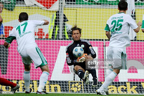 Goalkeeper Andre Lenz of Wolfsburg catches the ball while Alexander Madlung and Christian Gentner of Wolfsburg watch the scene during the Bundesliga...
