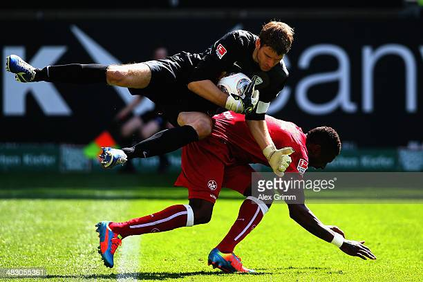 Goalkeeper Andreas Luthe of Bochum is challenged by Mohamadou Idrissou of Kaiserslautern during the Second Bundesliga match between 1 FC...