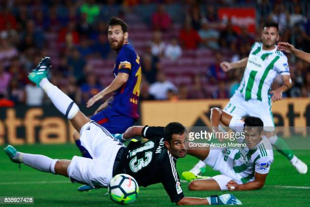 Goalkeeper Antonio Adan of Real Betis Balompie looses the ball striked by Lionel Messi of FC Barcelona as this scores their opening goal during the...