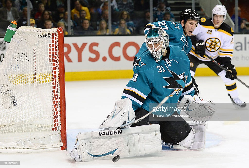 Goalkeeper Antti Niemi #31 of the San Jose Sharks makes a save, kicking the puck away from the net against the Boston Bruins during the first period at SAP Center on January 11, 2014 in San Jose, California.