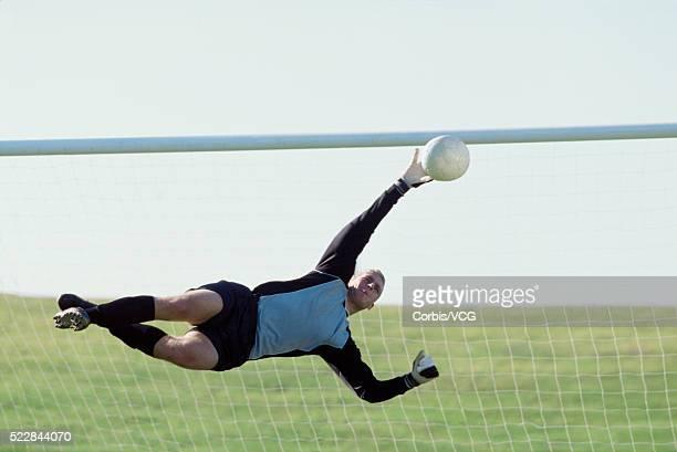 Goalkeeper attempting to prevent soccer goal
